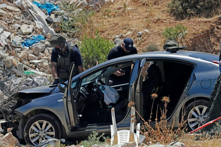 Israeli security forces inspect a vehicle following an attempted ramming and stabbing attack in the West Bank village of Hizma