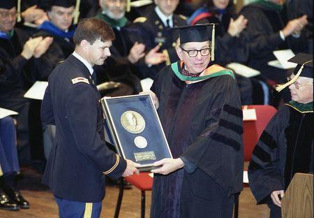 U.S. Army Medical Corps retired Lt. Colonel John Hagmann (L) is seen being presented the William P. Clements, Jr. Outstanding Uniformed Educator Award by Dr. Sam Nixon (R) during the U.S. Military's Uniformed Services University of the Health Sciences 1989 Commencement Exercises in this USUHS handout file photo taken in Washington May 20, 1989. REUTERS/Uniformed Services University of the Health Sciences Handout via Reuters