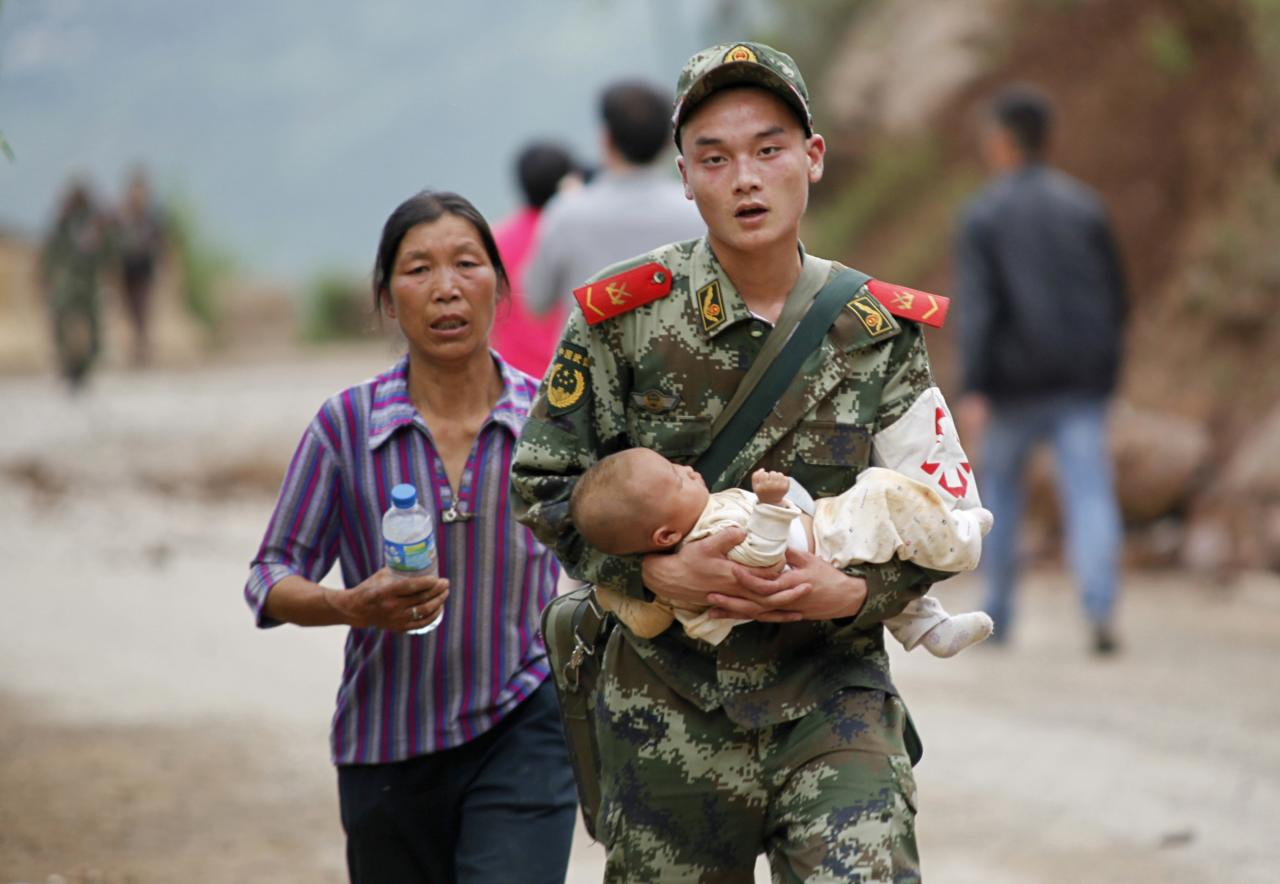 A paramilitary policeman carries a baby in his arms after an earthquake hit Ludian county of Zhaotong, Yunnan province August 3, 2014. The magnitude 6.5 earthquake struck southwestern China on Sunday, killing at least 175 people and leaving more than 180 missing and 1,400 injured in the remote area of Yunnan province, causing thousands of buildings, including a school, to collapse, Xinhua News Agency reported. REUTERS/China Daily (CHINA - Tags: DISASTER) CHINA OUT. NO COMMERCIAL OR EDITORIAL SALES IN CHINA