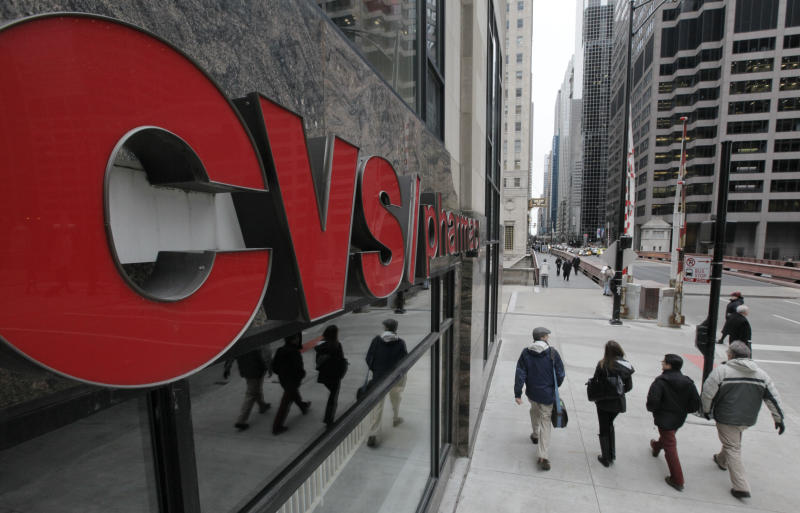 FILE - In this Feb. 7, 2012 file photo, pedestrians walk past a CVS store in Chicago. CVS Caremark Corp. is reporting their earnings on Wednesday, May 1, 2013.  (AP Photo/M. Spencer Green, File)
