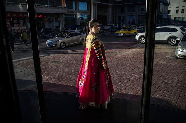 <p>A North Korean restaurant worker tries to attract customers in the border city of Dandong, Liaoning province, northern China across the Yalu River from the border city of Sinuiju, North Korea on May 23, 2017 in Dandong, China. (Photo: Kevin Frayer/Getty Images) </p>