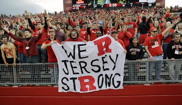 File-This Nov. 2, 2013, file photo shows Rutgers fans celebrating with five seconds left in the second half of an NCAA college football game against Temple in Piscataway, N.J. The musical chairs of conference realignment returns this this week, with more major colleges taking new seats. On Tuesday,July 1, 2014, 12 FBS teams officially switch places, including Louisville in the Atlantic Coast Conference and Maryland and Rutgers in the Big Ten. (AP Photo/Mel Evans, File)