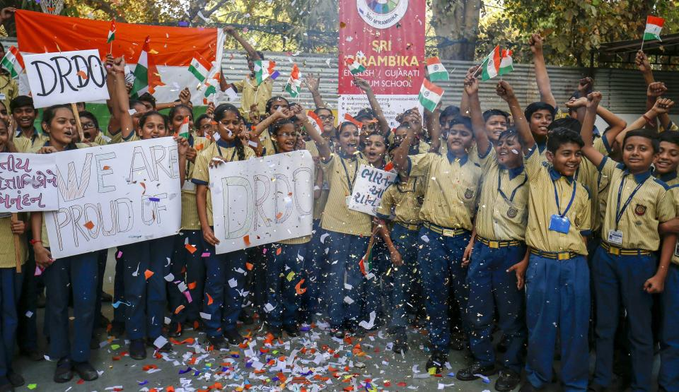 School students cheer as they hold flags and placards to celebrate the success of DRDO's Mission Shakti in Ahmedabad.