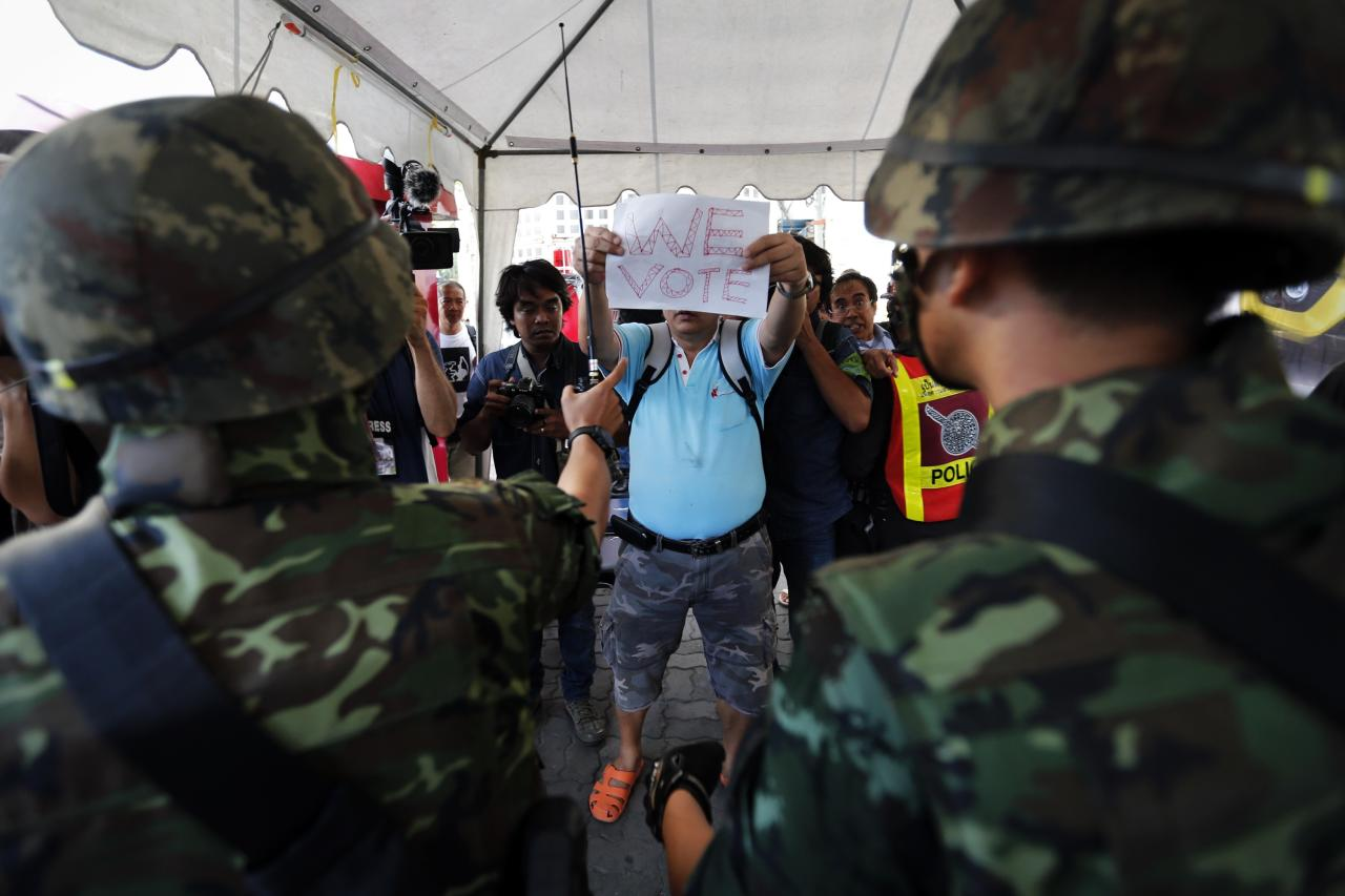 A man holds a sign as soldiers arrive to control a protest against military rule in central Bangkok, a day after the Thai army chief seized power in a coup May 23, 2014. Thai army chief General Prayuth Chan-ocha set out his plans for the country on Friday, a day after seizing power in a coup, saying reforms were needed before an election, but some Thais defied martial law to show opposition to his takeover. Several hundred people including students gathered in a central shopping district despite a ban on protests by five or more people to voice their opposition to military rule. REUTERS/Damir Sagolj (THAILAND - Tags: POLITICS CIVIL UNREST MILITARY)