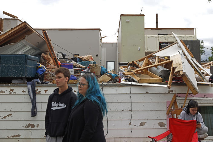 Woodridge, Ill., homeowners Bridget Casey and his son Nathan Casey, 16 stands in front of their damaged home after a tornado passed through the area on Monday, June 21, 2021. (AP Photo/Shafkat Anowar)