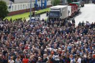 Workers listen to a speaker as they gather during a rally at the Minsk Automobile Plant in Minsk, Belarus, Friday, Aug. 14, 2020. Workers at the plant demanded a new election and called for the release of all those who were detained in a brutal police crackdown on demonstrators challenging the official results of Sunday's presidential vote. (AP Photo/Sergei Grits)