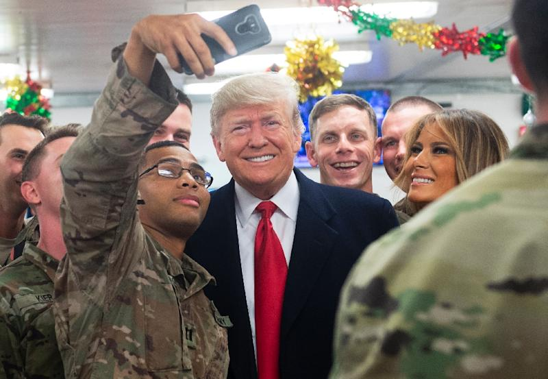 US President Donald Trump and First Lady Melania Trump greet members of the US military during a surprise Christmas trip to Al Asad Air Base in Iraq in December (AFP Photo/SAUL LOEB)