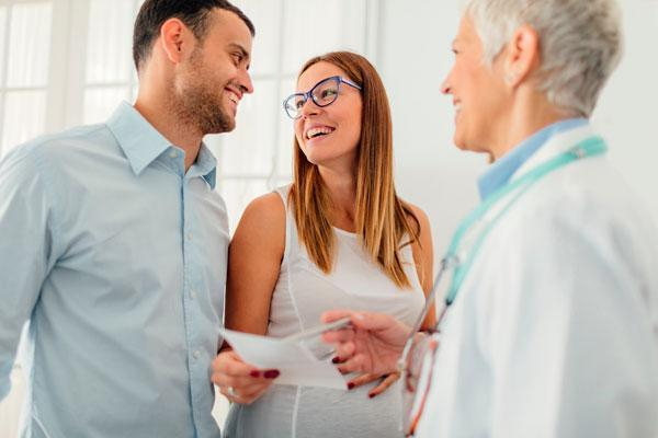 Pregnant woman and her female doctor in a consultation. Woman standing and holding ultrasound image and female doctor talking and pointing on image. Young woman husband is beside her and they are looking at each other.