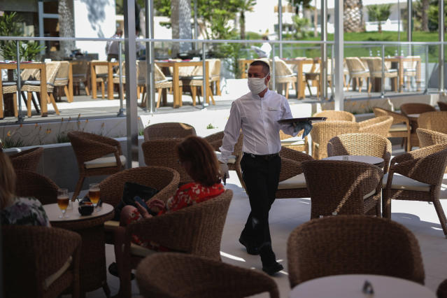 A waiter wearing protective face masks as a measure to help curb the spread of the new coronavirus in Mallorca. (AP)