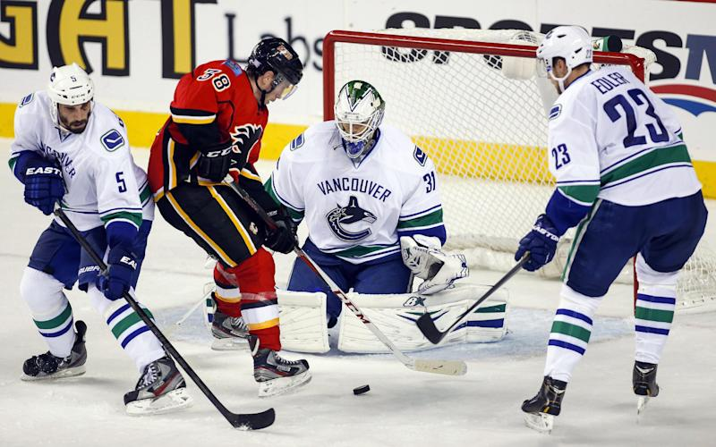 Vancouver Canucks goalie Eddie Lack, from Sweden, center, blocks the net on Calgary Flames' Ben Street, center left, as Canucks' Jason Garrison, left, and Alexander Edler, from Sweden, look on, during second period NHL hockey action in Calgary, Alberta, Sunday, Oct. 6, 2013. (AP Photo/The Canadian Press, Jeff McIntosh)