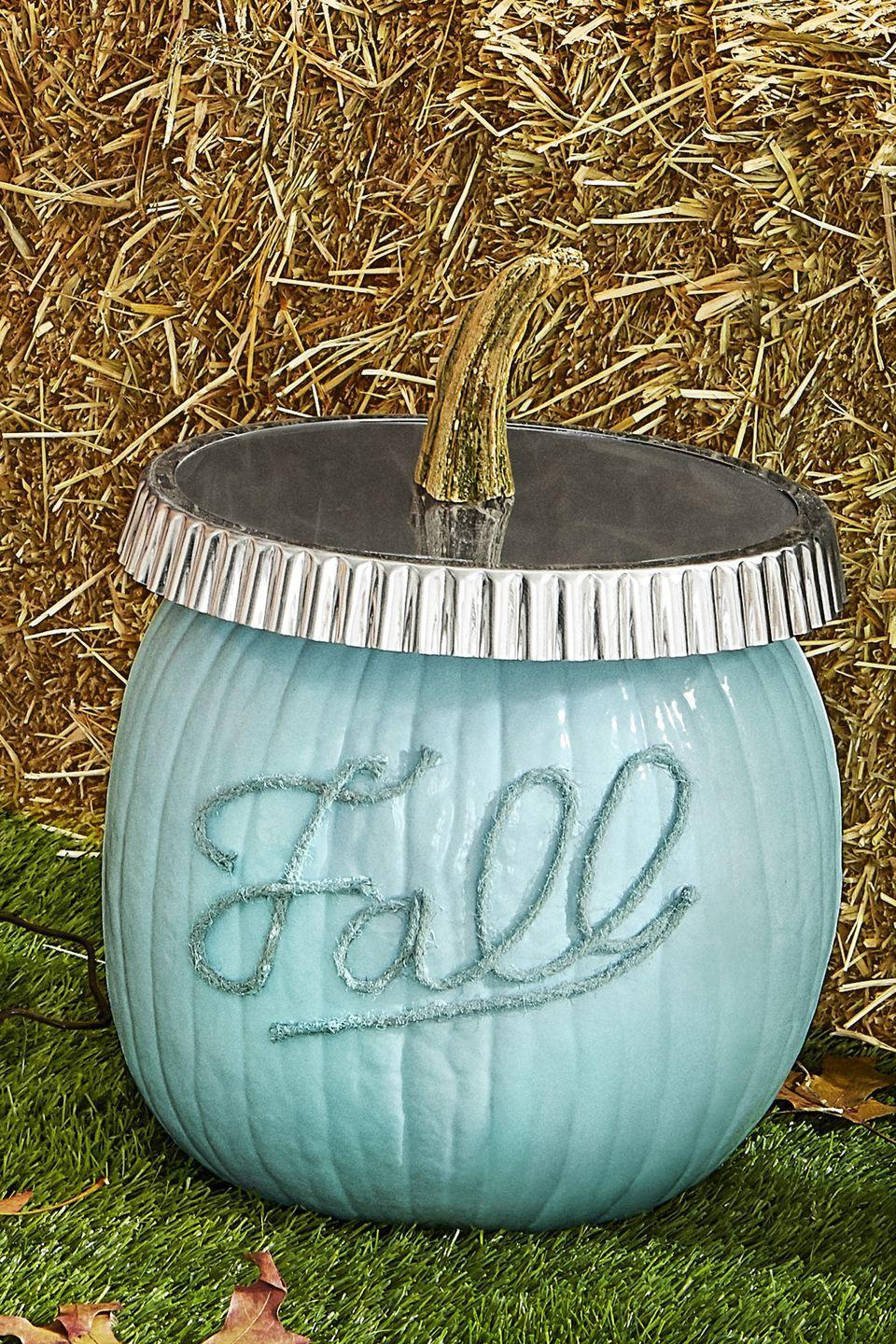 """<p>This pumpkin is the ultimate <a href=""""https://www.countryliving.com/diy-crafts/g1916/mason-jar-fall-crafts/"""" rel=""""nofollow noopener"""" target=""""_blank"""" data-ylk=""""slk:Mason jar craft"""" class=""""link rapid-noclick-resp"""">Mason jar craft</a>! Start by removing the stem of a medium pumpkin—but don't throw it away. Next, use wired twine to spell out """"fall"""" and hot-glue to the pumpkin. Paint the pumpkin and twine with light blue craft paint. Make sure it dries completely. Lastly, place a nine-to 10-inch tart pan upside down on the pumpkin. Hot-glue the reserved stem to the center of the pan. </p>"""