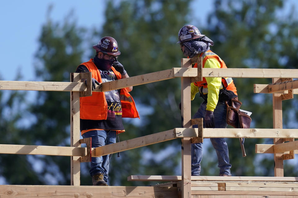 Construction workers talk at a USA Properties Fund site, Tuesday, Feb. 2, 2021, in Simi Valley, Calif. Hiring has weakened for six straight months. Nearly 10 million jobs remain lost since the coronavirus struck. And this week, the Congressional Budget Office forecast that employment won't regain its pre-pandemic level until 2024. (AP Photo/Mark J. Terrill)