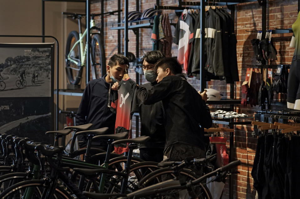 A man wearing a face mask to help curb the spread of the coronavirus checks on a cycling cloth with his friend at a bicycle retail shop selling American bicycle brand in Beijing on Tuesday, March 2, 2021. Chinese leaders are shifting focus from the coronavirus back to long-term goals of making China a technology leader at this year's highest-profile political event, the meeting of its ceremonial legislature, amid tension with Washington and Europe over trade, Hong Kong and human rights. (AP Photo/Andy Wong)