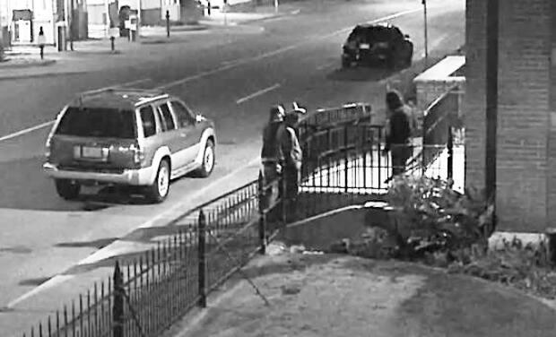 Victoria police posted video and images from the night a downtown church was vandalized that it says shows a potential witness speaking to the suspects. (Victoria Police Department - image credit)