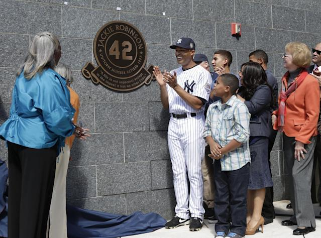 New York Yankees relief pitcher Mariano Rivera, along with his family, applauds as Jackie Robinson's daughter Sharon, far left, and wife Rachel, backs to camera, watch the unveiling of Robinson's monument in Monument Park during a pregame ceremony at Yankees Stadium before the Yankees baseball game against the San Francisco Giants, Sunday, Sept. 22, 2013, in New York. (AP Photo/Kathy Willens, Pool)