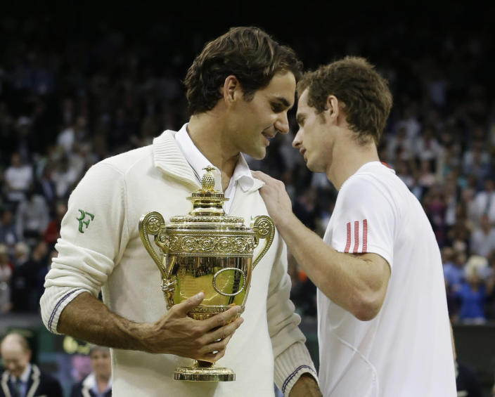 Andy Murray of Britain, right, congratulates Roger Federer of Switzerland, as he poses with his trophy following the men's singles final match at the All England Lawn Tennis Championships at Wimbledon, England, Sunday, July 8, 2012. (AP Photo/Kirsty Wigglesworth)