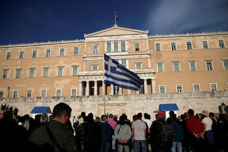A protester waves a Greek flag during a demonstration outside the parliament building in central Athens