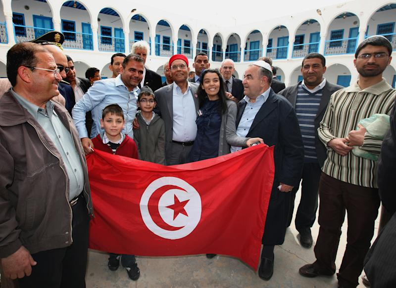 Tunisian President Moncef Marzouki, center, poses with a national flag and members of the Jewish community as he visits the synagogue on Djerba island, Tunisia Wednesday, April 11, 2012, to mark the 10th anniversary of an al-Qaida truck bomb at the synagogue that killed 21 people. It comes at a time when Tunisia's small, 1,500-strong, Jewish community is facing pressure from ultraconservative Muslim groups, after an uprising last year overthrew Tunisia's decades-old secular dictatorship. (AP Photo/Str)