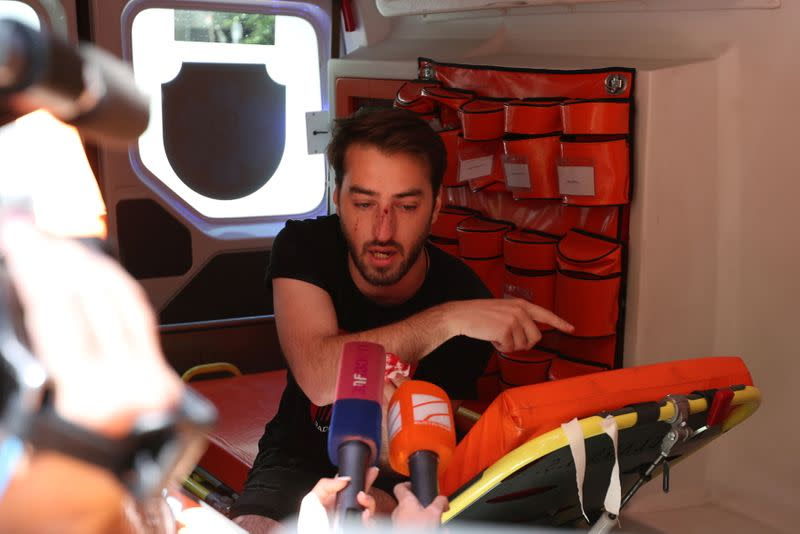 A journalist injured at a rally against the March for Dignity speaks to the media inside an ambulance in Tbilisi