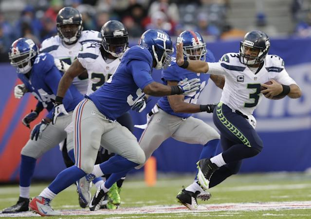 Seattle Seahawks quarterback Russell Wilson (3) stiff-arms New York Giants defensive end Justin Tuck (91) during the second half of an NFL football game on Sunday, Dec. 15, 2013, in East Rutherford, N.J. (AP Photo/Kathy Willens)