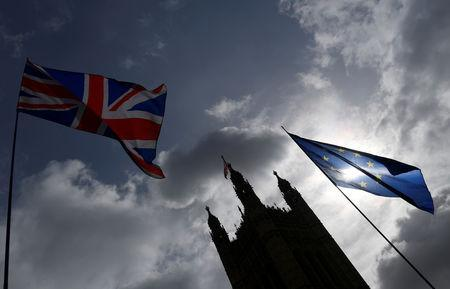 FILE PHOTO - The British union flag and the EU flag are seen flying near the Houses of Parliament, in London, Britain, March 18, 2019. REUTERS/Toby Melville