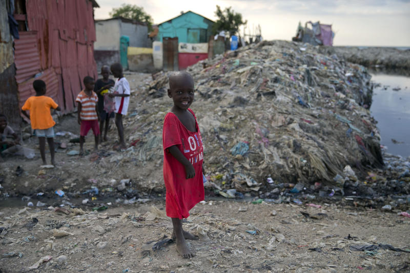 In this Dec. 3, 2019 photo, a boy stands near an open sewage canal in Cite Soleil slum of Port-au-Prince, Haiti. The boys was flying a kite along with his friends. The United Nations recently said 3.7 million people are facing emergency levels of food insecurity, including 1 million who are at stage four, one level below famine. (AP Photo/Dieu Nalio Chery)