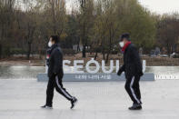 People wearing face masks as a precaution against the coronavirus walk past the display of South Korea's capital Seoul logo at a park in Seoul, South Korea, Tuesday, Nov. 24, 2020. Authorities in the South Korean capital on Monday announced a tightening of social distancing regulations, including shutting nightclubs, limiting service hours at restaurants and reducing public transportation. (AP Photo/Lee Jin-man)