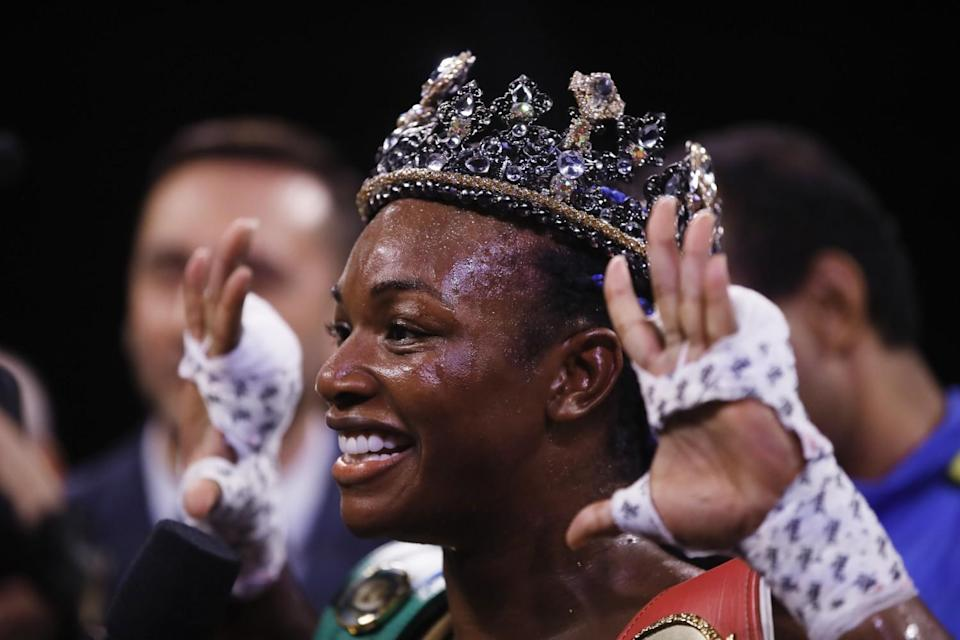 Claressa Shields smiles and wears a crown while showing her wrapped hands.