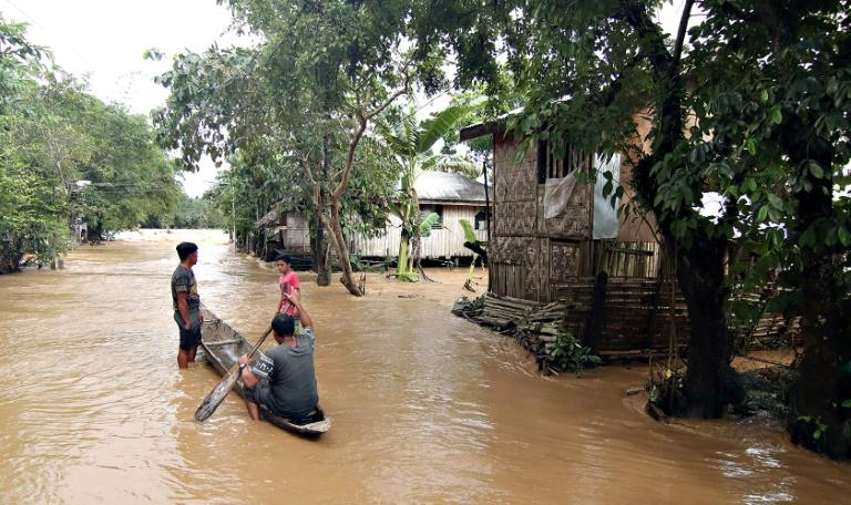 Residents use a canoe to survey their village after it was flooded by Tropical Storm Sanba in the town of Jaboanga on  Mindanao island on February 13