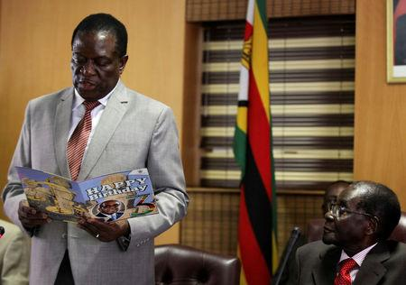FILE PHOTO: Zimbabwe's President Robert Mugabe looks on as his deputy Emmerson Mnangagwa reads a card during Mugabe's 93rd birthday celebrations in Harare