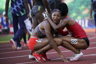 Gabby Thomas, left, celebrates after winning the final in the women's 200-meter run with Anavia Battle at the U.S. Olympic Track and Field Trials Saturday, June 26, 2021, in Eugene, Ore. (AP Photo/Ashley Landis)