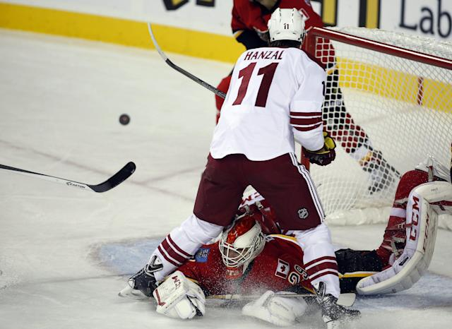 Phoenix Coyotes' Martin Hanzal, top, from the Czech Republic, stumbles over Calgary Flames goalie Reto Berra, bottom, from Switzerland, during second-period NHL preseason hockey game action in Calgary, Alberta, Wednesday, Sept. 25, 2013. (AP Photo/The Canadian Press, Jeff McIntosh)