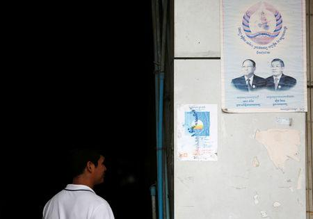 A man walks near posters the Cambodia National Rescue Party (CNRP) and Cambodian People's Party (CPP), in Phnom Penh, Cambodia, November 20, 2017. REUTERS/Samrang Pring