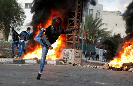 Palestinian demonstrator hurls stones toward Israeli troops during clashes at a protest near the West Bank city of Nablus