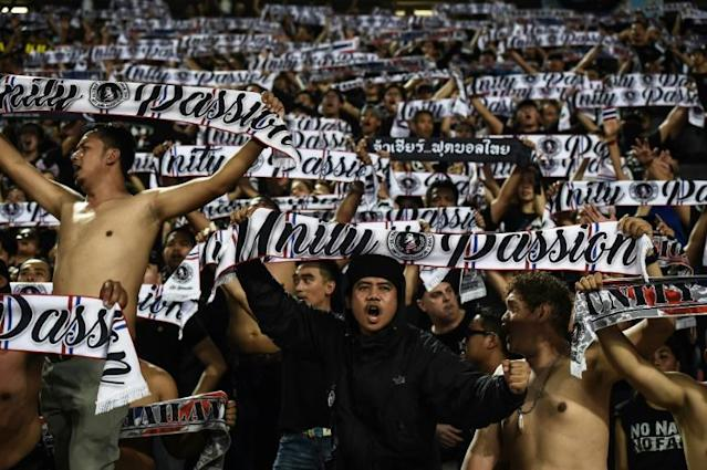 Thai football fans wave scarves in unison during a World Cup qualifying match: now the domestic league has been hit by match-fixing claims