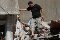 Syrian refugee Ahmed Staifi walks among the debris of a house were his wife and two of his daughters were killed following a massive explosion, in Beirut