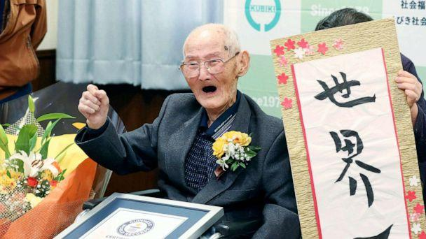 PHOTO: Chitetsu Watanabe, 112, poses next to the calligraphy he wrote after being awarded as the world's oldest living male by Guinness World Records, in Joetsu, Niigata prefecture, northern Japan Feb. 12, 2020. (Kyodo News via AP)