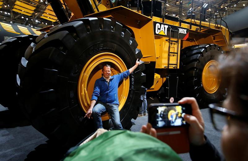A man poses in a wheel of a Caterpillar excavator at the 'Bauma' Trade Fair for Construction Machinery, Building Material Machines, Mining Machines, Construction Vehicles and Construction Equipment in Munich, Germany, April 8, 2019. REUTERS/Michaela Rehle