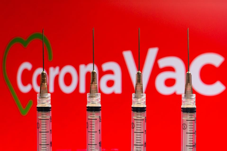 BRAZIL - 2020/12/04: In this photo illustration various medical syringes seen with Coronavac company logo displayed on a screen in the background. (Photo Illustration by Rafael Henrique/SOPA Images/LightRocket via Getty Images)
