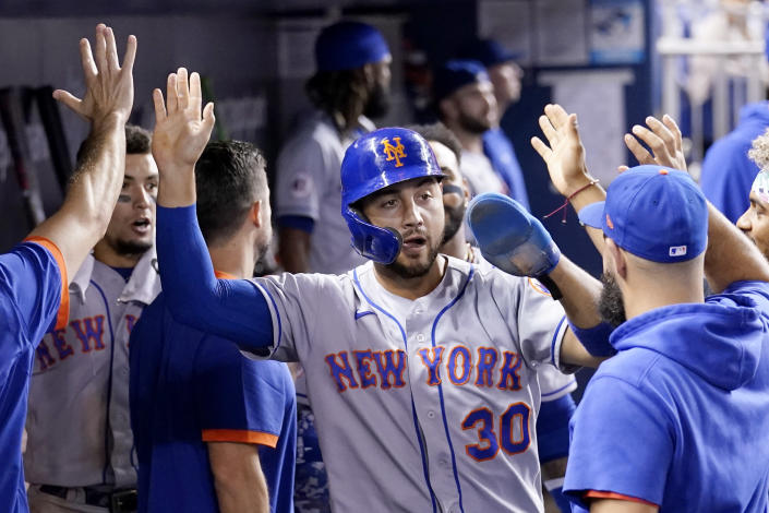 New York Mets' Michael Conforto is congratulated in the dugout after scoring on a passed ball by Miami Marlins catcher Alex Jackson during the eighth inning of a baseball game, Wednesday, Aug. 4, 2021, in Miami. The Mets won 5-3. (AP Photo/Lynne Sladky)