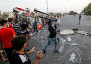 Protesters erect a makeshift barricade during clashes with Iraqi security forces after a demonstration against corruption and lack of basic services including electricity in the southern city of Basra