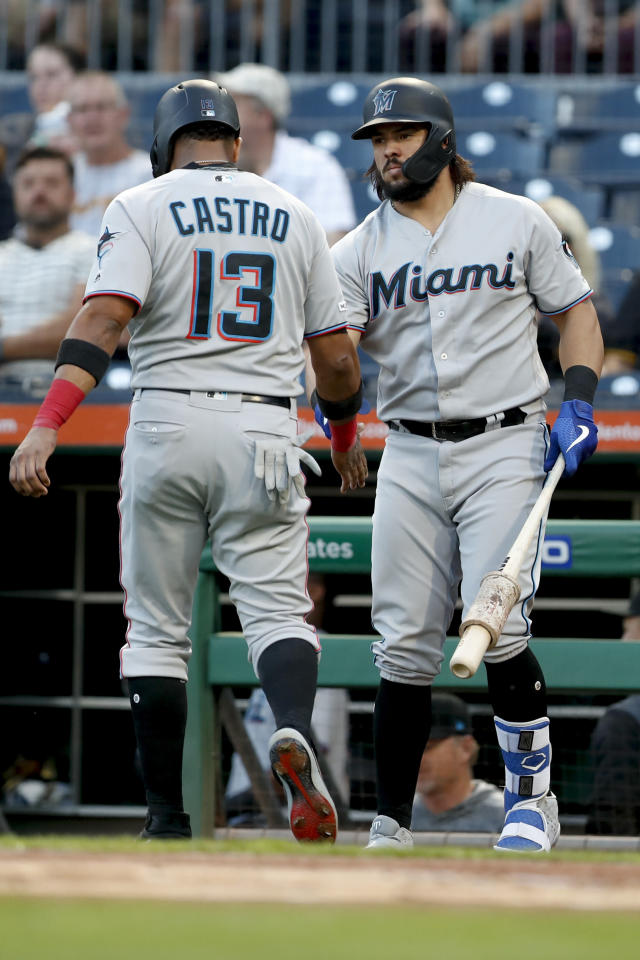 Miami Marlins' Starlin Castro (13) is greeted by on-deck batter Jorge Alfaro after he scored from second on a double by Garrett Cooper during the first inning of the team's baseball game against the Pittsburgh Pirates, Wednesday, Sept. 4, 2019, in Pittsburgh. (AP Photo/Keith Srakocic)