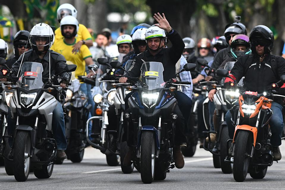 Brazilian President Jair Bolsonaro (C) gestures as he heads a motorcade rally with his supporters in Rio de Janeiro, Brazil, on May 23, 2021. - Bolsonaro led a procession of several thousand motorcycles that marched through the streets of Rio de Janeiro for a demonstration in his support, sparking numerous demonstrations amid the pandemic. (Photo by ANDRE BORGES / AFP) (Photo by ANDRE BORGES/AFP via Getty Images)