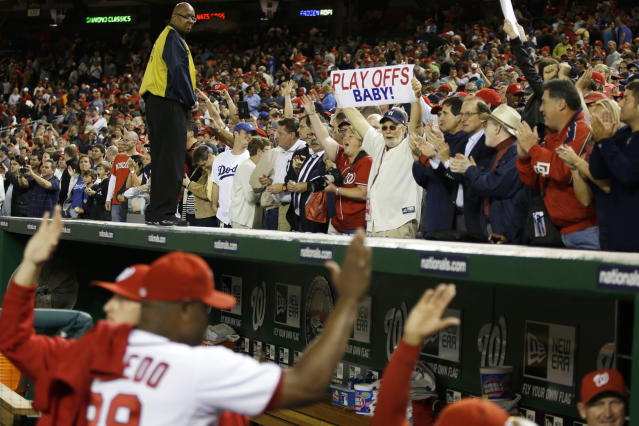 Washington Nationals players high-five as fans celebrate their 4-1 win against the Los Angeles Dodgers to clinch a playoff spot after their baseball game at Nationals Park in Washington, Thursday, Sept. 20, 2012. (AP Photo/Jacquelyn Martin)