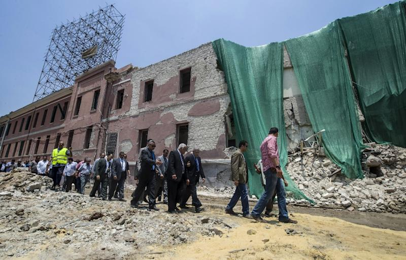 Egyptian Prime Minister Ibrahim Mahlab and other officials walk past the bombed compound of the Italian consulate in Cairo on July 13, 2015 (AFP Photo/Khaled Desouki)