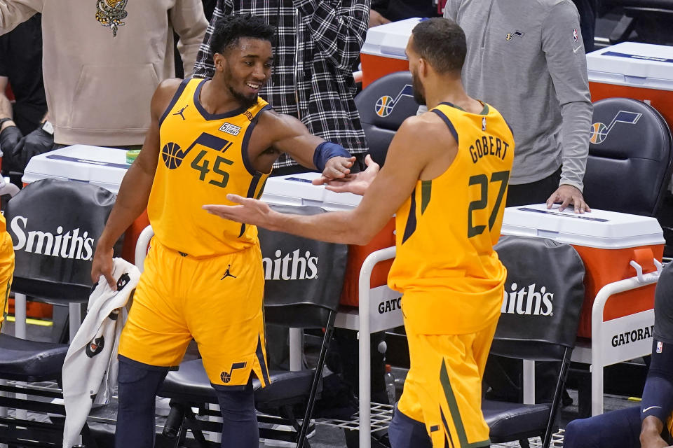 Utah Jazz's Donovan Mitchell (45) celebrates with Rudy Gobert (27) after leaving the game during the second half of the team's NBA basketball game against the New Orleans Pelicans on Tuesday, Jan. 19, 2021, in Salt Lake City. (AP Photo/Rick Bowmer)