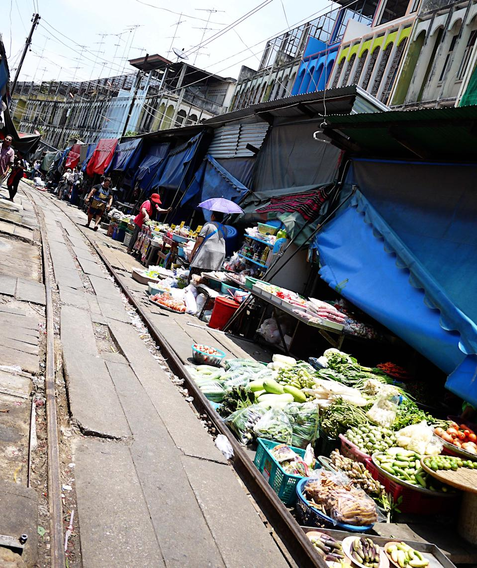 <p>But if you look down on the road, you'll realise that you're actually walking on train rails! And when you hear a siren, it's time to step back into safety and let the action unfold. One moment, locals are shopping for the vegetables; the next they are waiting patiently at the side while stall keepers are scooping up their baskets and boxes of goods with a rather lackadaisical attitude about the whole exercise. Tourists are of course the most excited as they set up their cameras so they don't miss the action.</p>