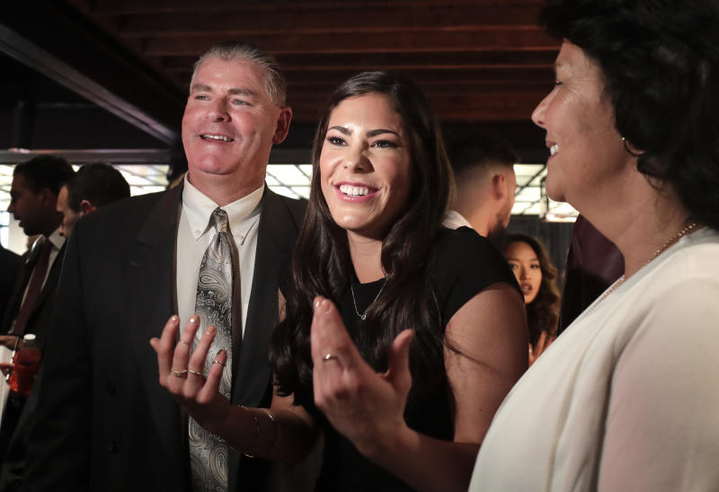 Washington guard Kelsey Plum, center, speaks to a television crew alongside her father, Jim, left, and mother, Katie, before the WNBA basketball draft, Thursday, April 13, 2017, in New York. (AP Photo/Julie Jacobson)