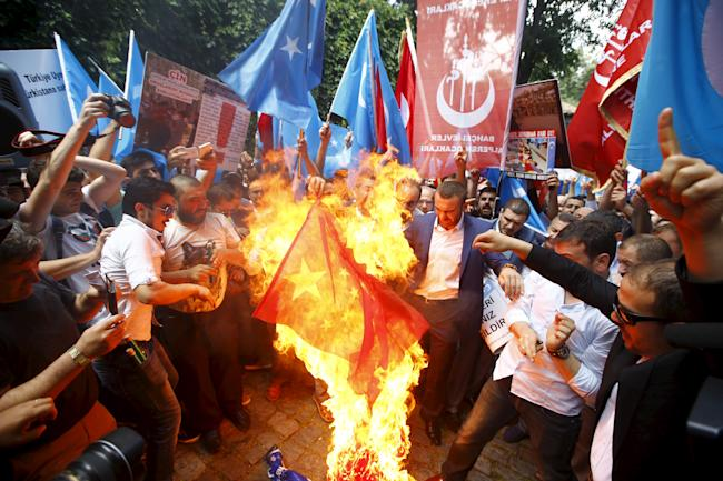 Demonstrators set fire to a Chinese flag during a protest against China near the Chinese Consulate in Istanbul, Turkey, July 5, 2015.