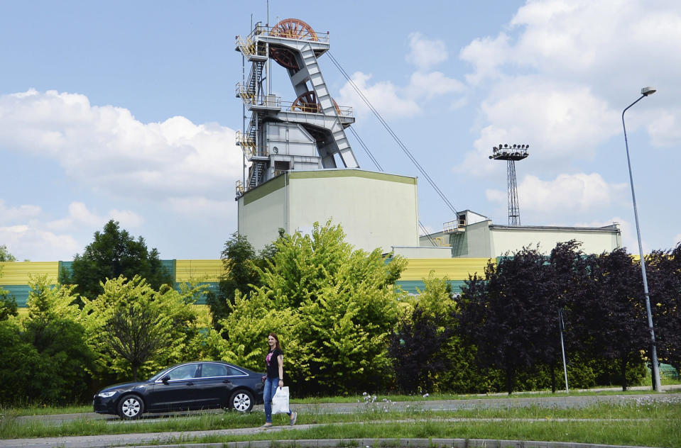 A woman passes the Wujek coal mine in the Polish region of Silesia during a pause in operations in Katowice, Poland, Saturday, July 4, 2020. The coronavirus has ripped through Poland's coal mines, paralyzing an already-troubled industry, forcing many to stay home from work and triggering a three-week closure of many state-run mines. (AP Photo/Czarek Sokolowski)